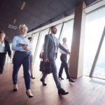 Four person business team walking through a brightly lit hallway